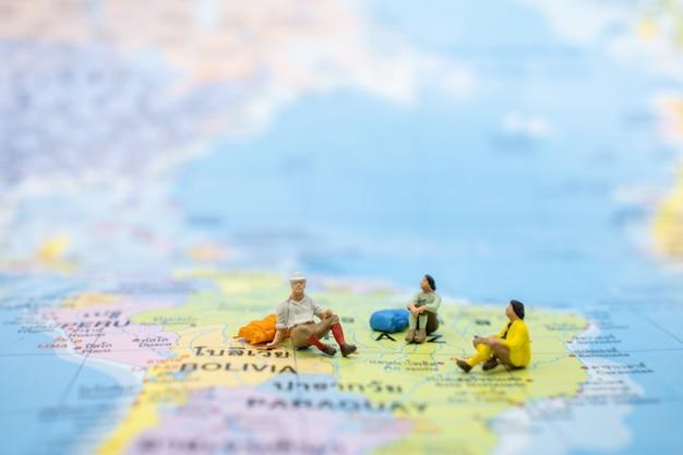 Gros groupe voyageur avec sac à dos assis sur une carte colorée. Photo Premium