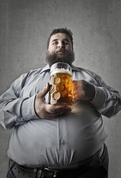 Gros homme ayant une bière Photo Premium