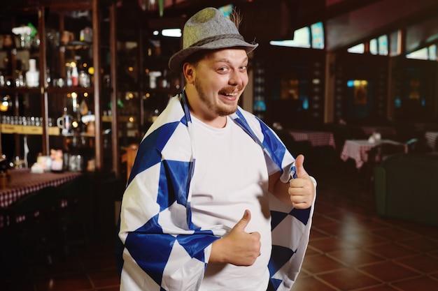 Gros homme gai avec un gros ventre avec un drapeau oktoberfest et un chapeau bavarois sur un fond de pub Photo Premium