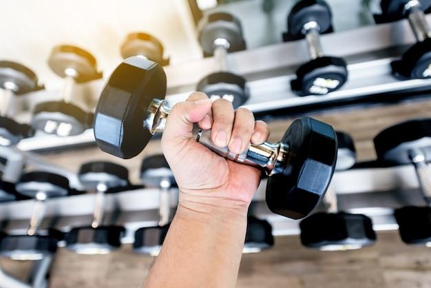 Gros homme main tenant des haltères en métal noir dans la salle de gym Photo Premium