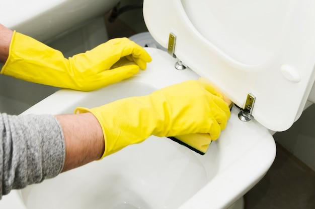 Gros homme nettoyant les toilettes avec une éponge Photo gratuit
