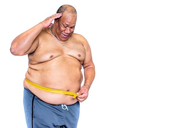 Un gros homme noir mesure sa taille inquiète avec un ruban à mesurer pour voir s'il a maigri avec le concept de régime .health and obesity Photo Premium