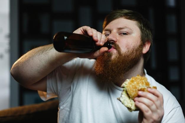 Gros homme regarde la télé, mange un hamburger et boit de la bière Photo gratuit