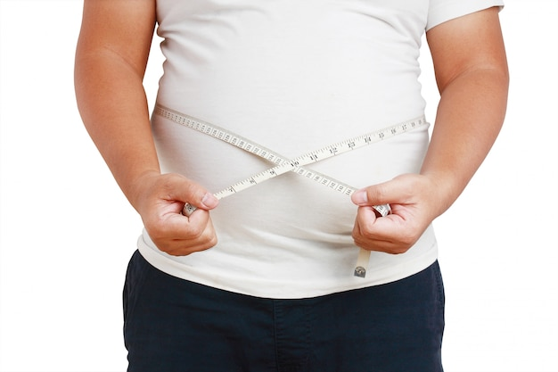 Le gros homme, le ventre est très gros, debout en utilisant le ruban à mesurer autour de sa taille Photo Premium