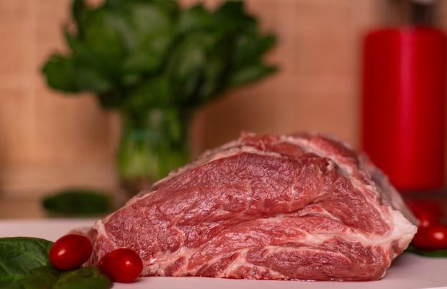 Gros morceau de viande de porc crue rouge, tomates cerises et verdure Photo Premium