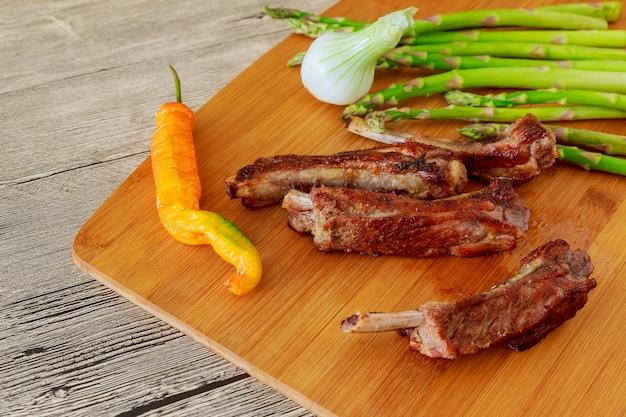 Gros morceaux de côtes de viande de bœuf cuits au four émaillés sous une sauce sucrée avec tomates piment rose Photo Premium