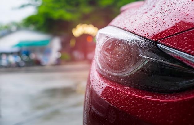 Gros phare d'une voiture moderne rouge avec une goutte de pluie sur fond flou. Photo Premium