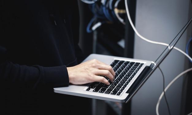 Gros plan d'un administrateur travaillant sur un ordinateur portable dans un centre de données Photo Premium