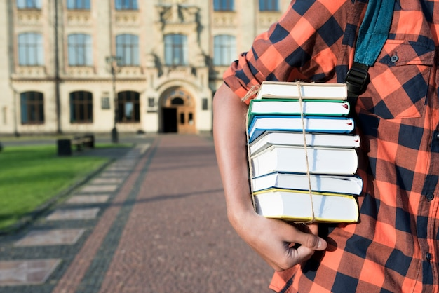 Gros plan d'un adolescent tenant des livres sous son bras Photo gratuit