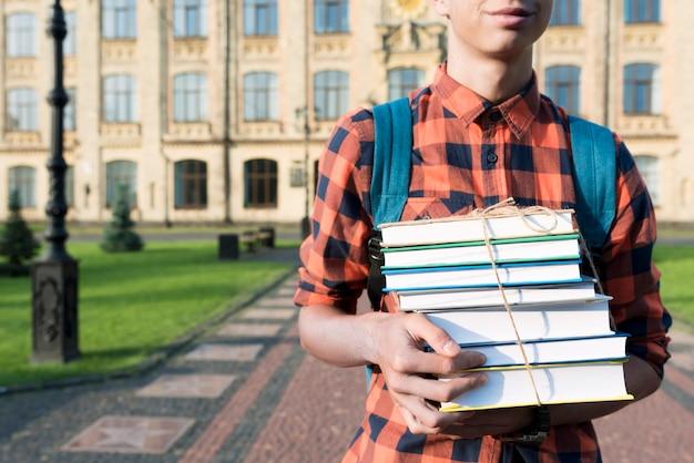 Gros plan d'un adolescent tenant des livres Photo gratuit