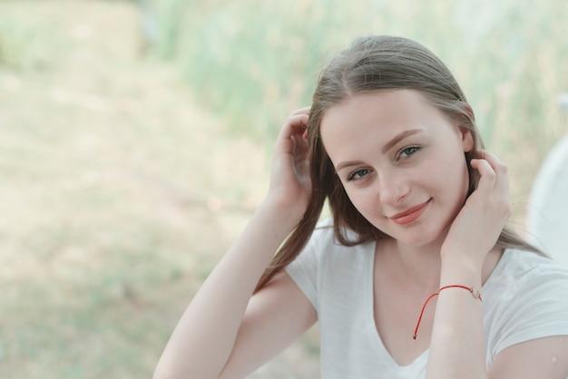 Gros plan d'une adolescente assise, se détendre dans le parc, sur un banc. l'éducation, fille d'école. jeune femme souriante. heure d'été, en plein air. Photo Premium