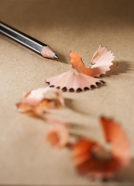Gros plan aiguiser un crayon noir sur du papier brun Photo Premium