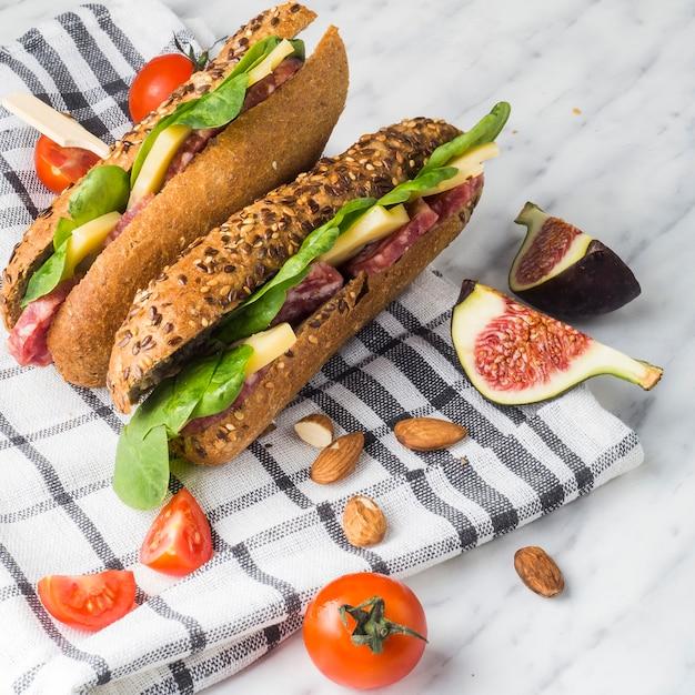Gros plan d'amandes; tomates cerises; tranches de figue et des hot-dogs en bonne santé avec une serviette à carreaux sur fond blanc Photo gratuit