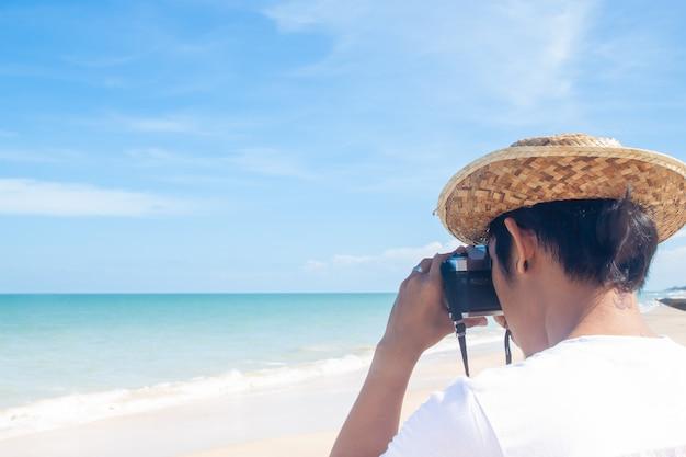 Gros plan, arrière, vue, homme asiatique, tir, photo, sur, plage, bonnes vacances Photo Premium