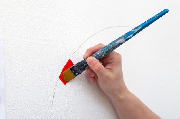 Gros plan d'une artiste féminine dessine sur un mur avec un grand gland en bois rouge Photo Premium