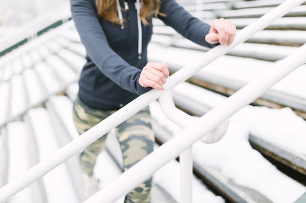 Gros plan d'athlète féminine exerçant sur un escalier en hiver Photo gratuit