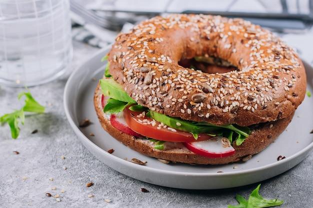 Gros plan de bagels aux légumes sur une assiette. fond de table en béton. déjeuner sain. délicieux repas équilibré Photo Premium