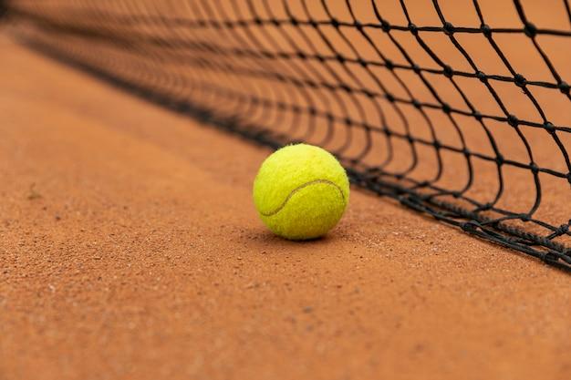Gros plan d'une balle de tennis à côté du filet Photo gratuit