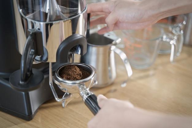 Gros Plan Sur Le Barista Tirant Le Levier De La Machine à Moudre Pour Obtenir Le Grain De Café Moulu Dans Le Tampon De Café. Photo Premium