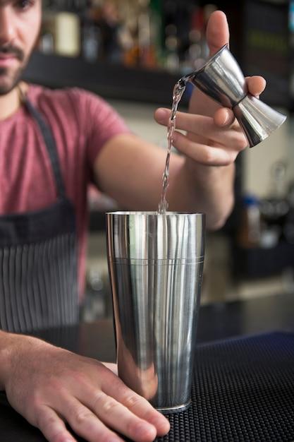 Gros plan, barman, verser, cocktail, dans, shaker, à, comptoir bar Photo gratuit