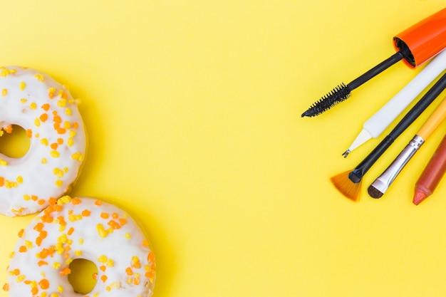 Gros plan de beignets blancs avec pinceau de maquillage; rouge à lèvres; mascara et cuticule sur fond jaune Photo gratuit