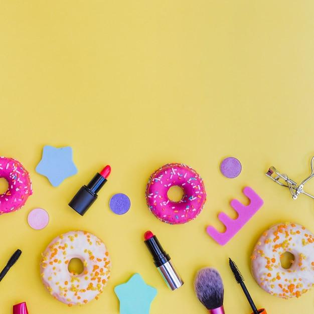 Gros plan des beignets; rouge à lèvres; recourbe-cils; pinceau de maquillage et séparateur d'orteil sur fond jaune Photo gratuit
