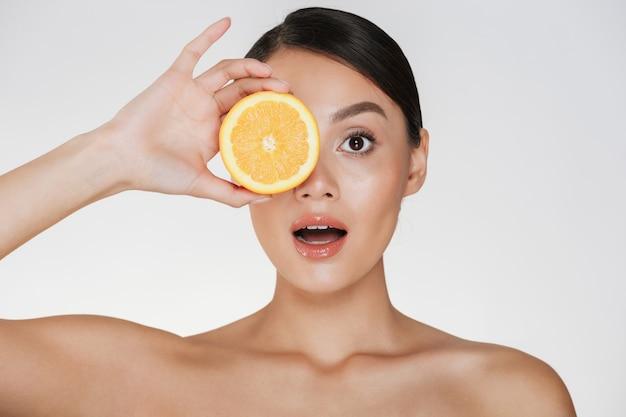 Gros Plan De La Belle Dame à La Peau Douce Et Douce Tenant Une Orange Juteuse, Appréciant La Vitamine Naturelle Isolée Sur Blanc Photo gratuit