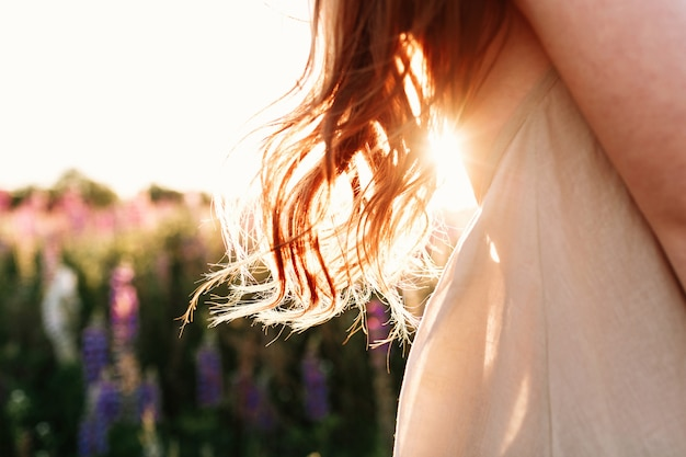 Gros plan de belle femme mèche de cheveux sur fond de coucher de soleil dans le champ de la fleur. Photo gratuit