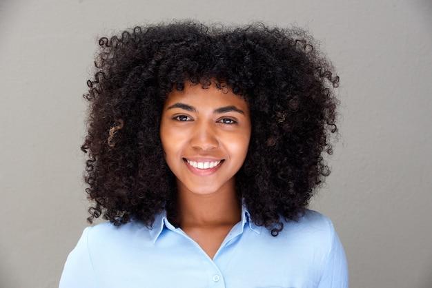 Gros plan belle jeune femme africaine souriante sur fond gris Photo Premium