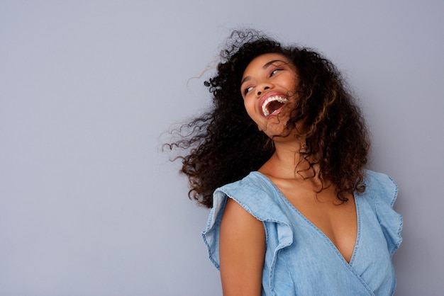 Gros plan belle jeune femme noire rire contre le mur gris Photo Premium