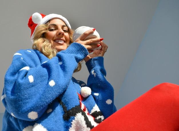 Gros Plan D'une Belle Jeune Femme Portant Une Robe De Noël Et Un Chapeau Tenant Une Tasse De Santa Photo gratuit