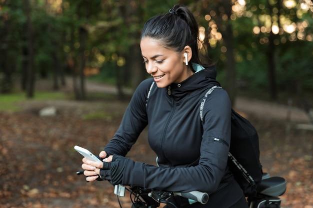 Gros Plan D'une Belle Jeune Femme De Remise En Forme à Cheval Sur Un Vélo Dans Le Parc, écouter De La Musique Avec Des écouteurs, Tenant Un Téléphone Mobile Photo Premium