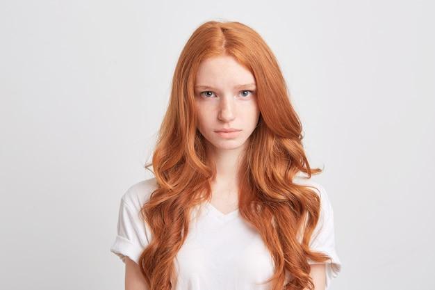 Gros Plan De La Belle Jeune Femme Rousse Aux Cheveux Longs Ondulés Et Taches De Rousseur Porte T-shirt Se Sent Triste Et Regarde à L'avant Isolé Sur Un Mur Blanc Photo gratuit
