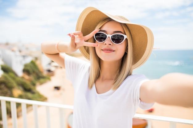 Gros Plan D'une Belle Jeune Fille Au Chapeau D'été Prenant Un Selfie Et Montrant Le Geste De Paix à La Plage Photo gratuit