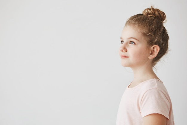 Gros Plan D Une Belle Petite Fille Aux Cheveux Blonds En Coiffure Chignon Debout Dans Les Trois Quarts Regardant De Cote Avec Le Sourire Sur Son Visage Photo Gratuite