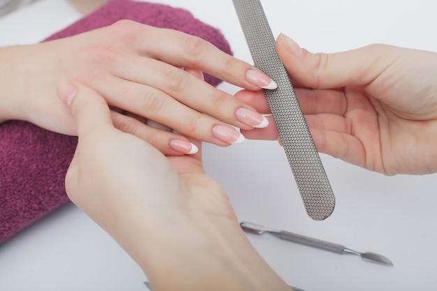 Gros plan de belles mains féminines ayant manucure spa au salon de beauté Photo Premium