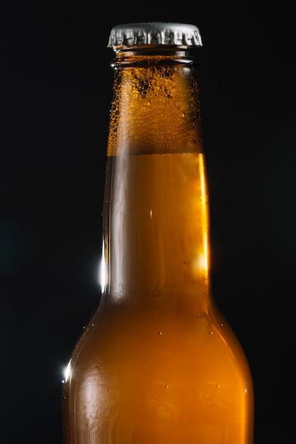 Gros plan, de, a, bière, bouteille, sur, arrière-plan noir Photo gratuit