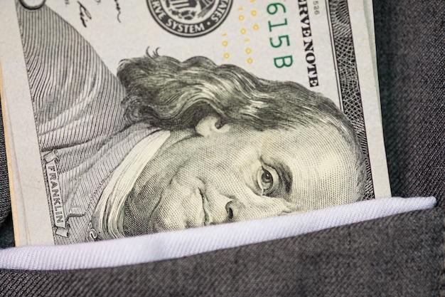 Gros plan d'un billet en dollars américains dans la poche d'un costume gris. concept d'investissement et de paiement. Photo Premium