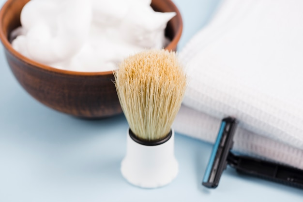 Gros plan d'un blaireau classique; mousse; serviette blanche et rasoir sur fond bleu Photo gratuit