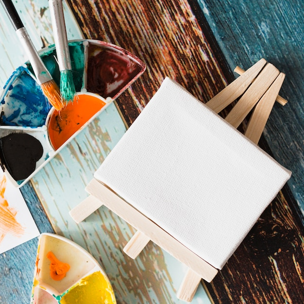 Gros plan, blanc, minimum, blanc, chevalet, à, palette peinture, et, pinceau, sur, surface bois Photo gratuit