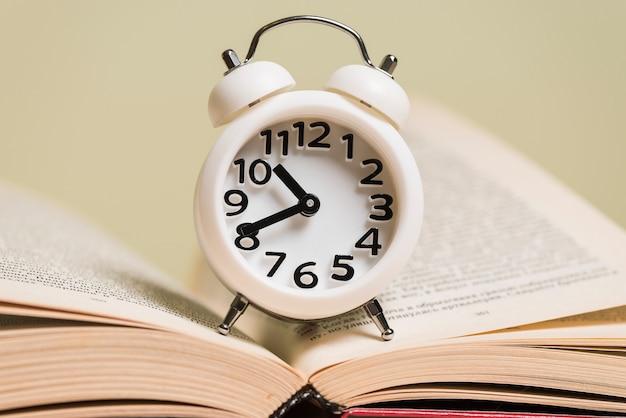Gros plan, blanc, réveil, sur, a, livre ouvert Photo gratuit
