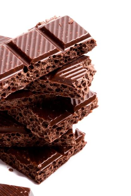 Gros plan de blocs de chocolat noir sur fond blanc Photo Premium