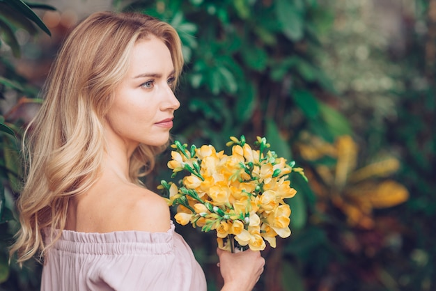 Gros plan d'une blonde jeune femme tenant un bouquet de fleurs jaunes à la main Photo gratuit