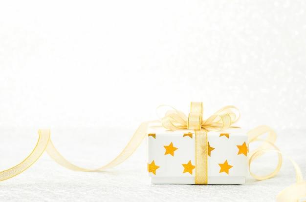 Gros Plan D'une Boîte-cadeau Blanche Avec Motif étoile Dorée Et Noeud De Ruban D'or Photo Premium