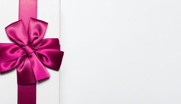 Gros Plan D'une Boîte Cadeau Blanche Avec Noeud Rose Isolé Sur Une Surface Blanche Photo Premium