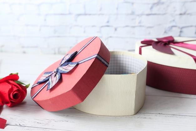 Gros Plan De Boîte-cadeau En Forme De Coeur Et Rose Rouge Sur La Table. Photo Premium