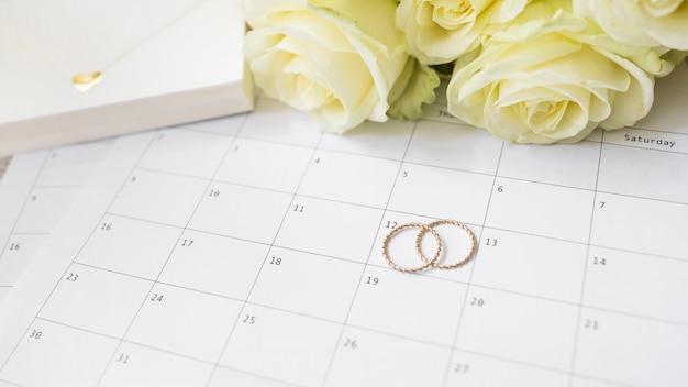 Gros plan de la boîte-cadeau; roses et alliances sur calendrier Photo gratuit