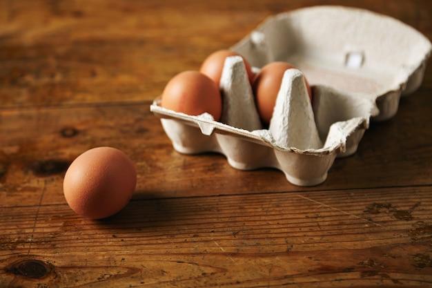 Gros Plan D'une Boîte à œufs Recyclable Ouverte Avec 3 œufs à L'intérieur Et Un œuf à Côté Sur Une Table En Bois Granuleux Brun Photo gratuit