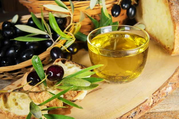 Gros Plan D'un Bol En Verre Plein D'huile D'olive Avec Du Pain Et Des Brunchs Aux Olives. Graisses Saines Photo Premium