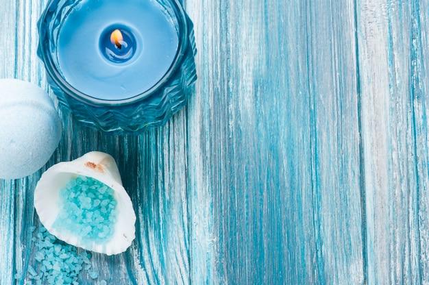 Gros plan de bombes de bain avec une bougie allumée bleue Photo Premium